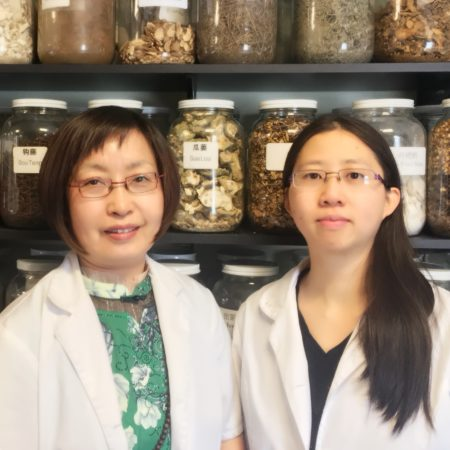 Drs. Anna Diec and Nawei Jiang wearing white lab coats standing in front of shelves stocked with jars of herbs