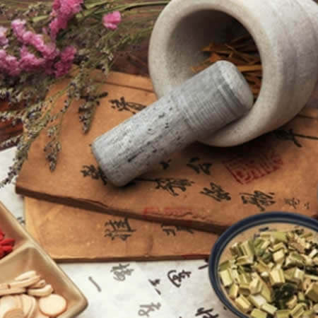 Gray pestle and mortar stone surrounded by pink flowers and different herbs